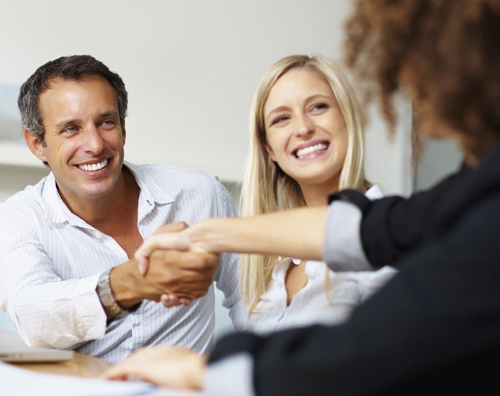Business man shaking hands with female colleague and smiling during meeting